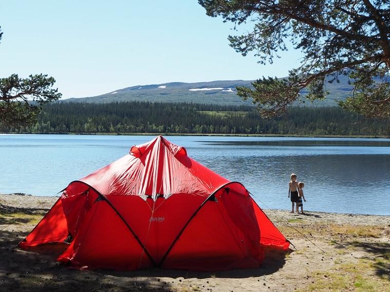 Rött tält på en sandstrand med berg i bakgrunden.