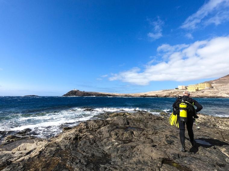 Dykare som gör sig redo för dykning på en klippa vid havet.