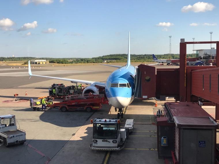 Flygplan som står vid gate och lastas med bagage.