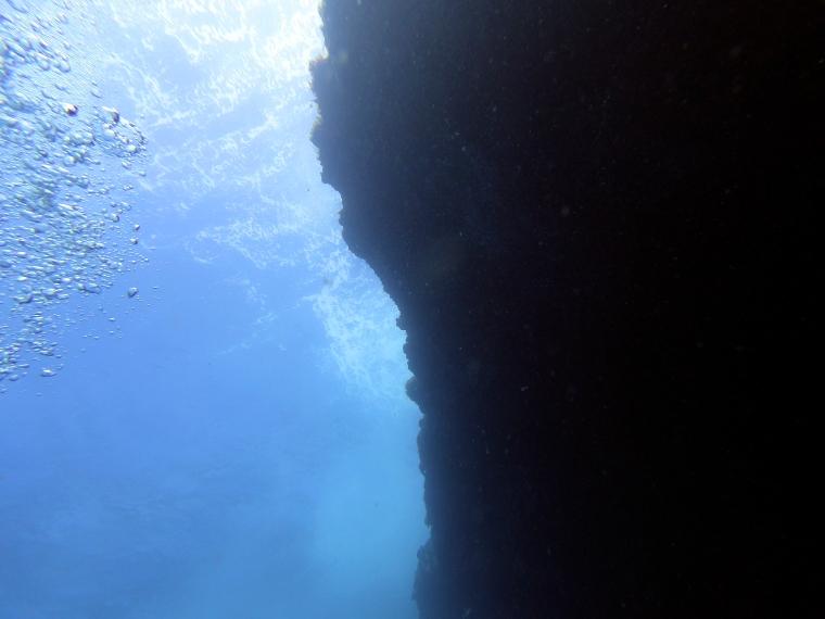 En klippa under vattnet i motljus.