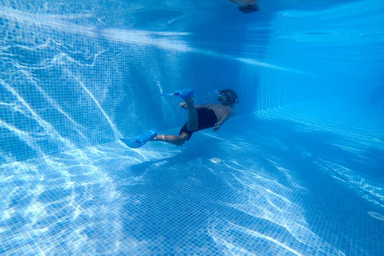 Barn simmande under vattnet i en pool bort från fotografen.
