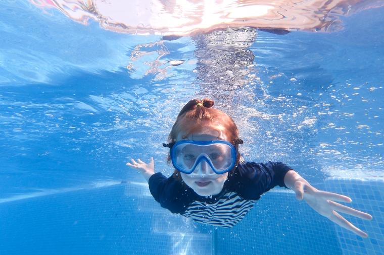 Barn simmande i pool mot fotografen.