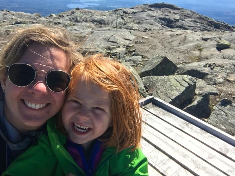 En vuxen och ett barn tar en selfie, utsikt i bakgrunden.