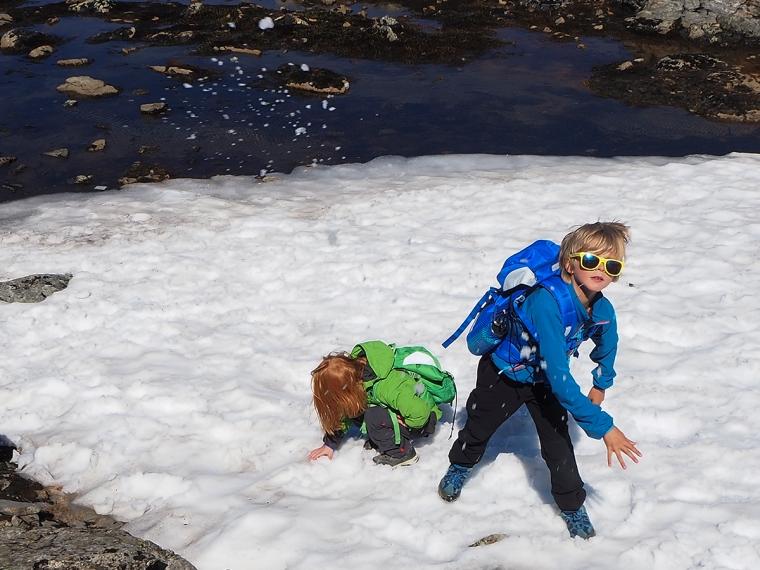 Två barn kastar snöbollar.