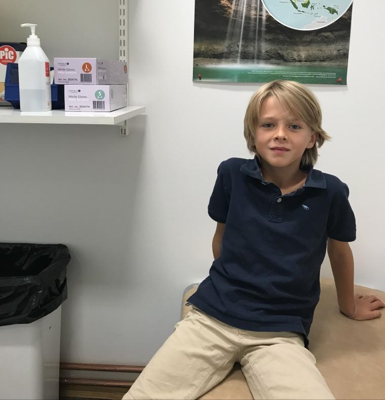 Ett barn sitter på en brits i ett undersökningsrum.