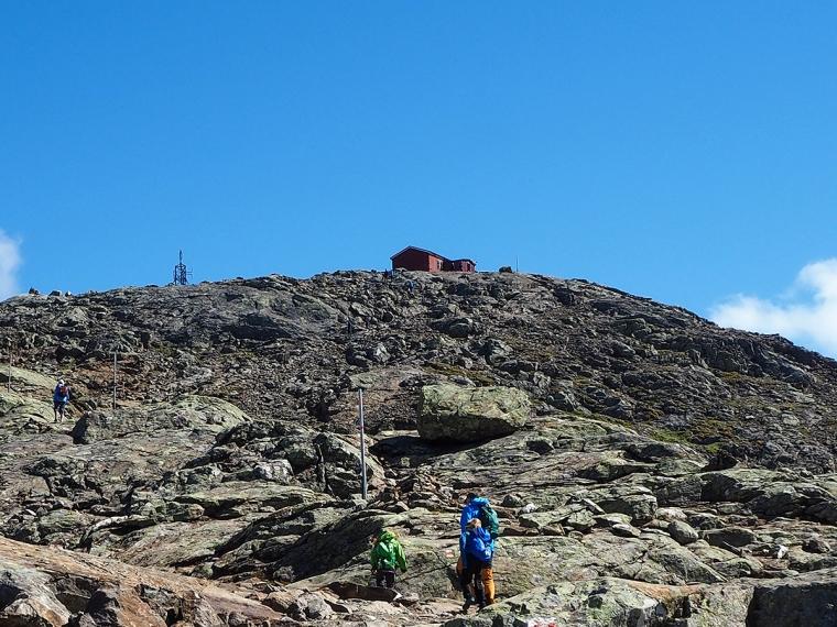 Tre personer vandrar mot en bergstopp med en röd stuga på toppen.