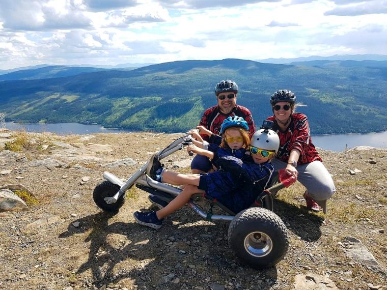 Två vuxna, två barn och en mountain cart med vacker utsikt i bakgrunden.