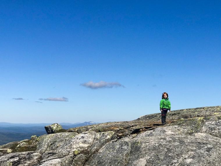 Ett barn uppe på Åreskutan med utsikt i bakgrunden.