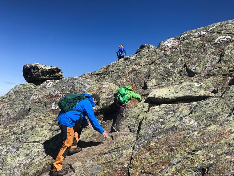 En vuxen och två barn klättrar på en bergsvägg.