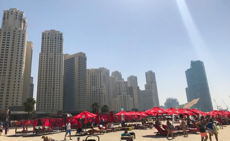 Bild på en sandstrand med skyskrapor i bakgrunden