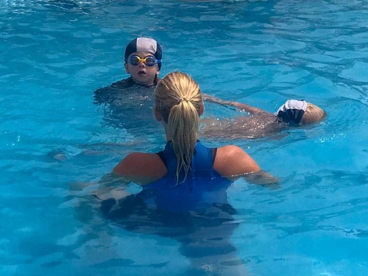 Barn och simlärare i pool.