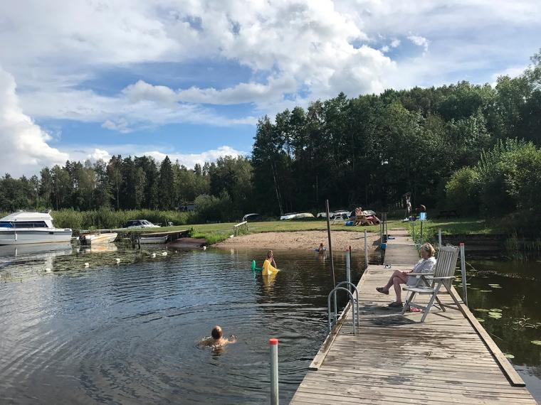 En brygga och barn som leker i vattnet.