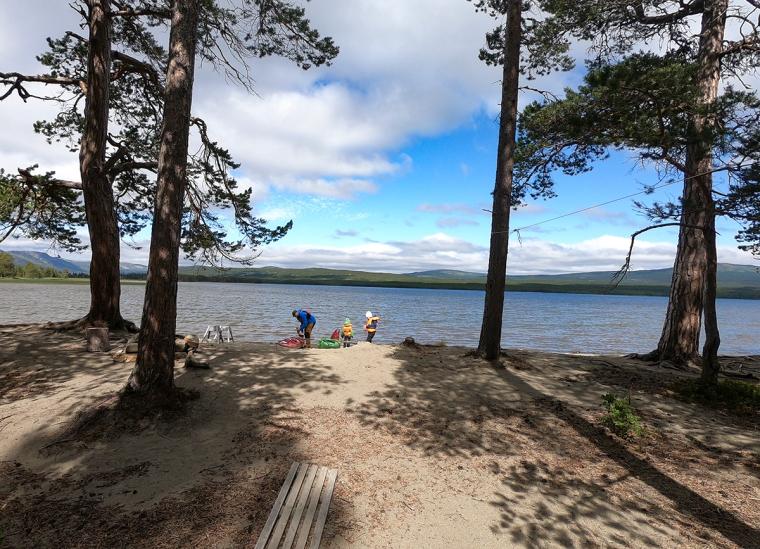 En vuxen och två barn fixar med två kajaker. Sjö och fjäll i bakgrunden.