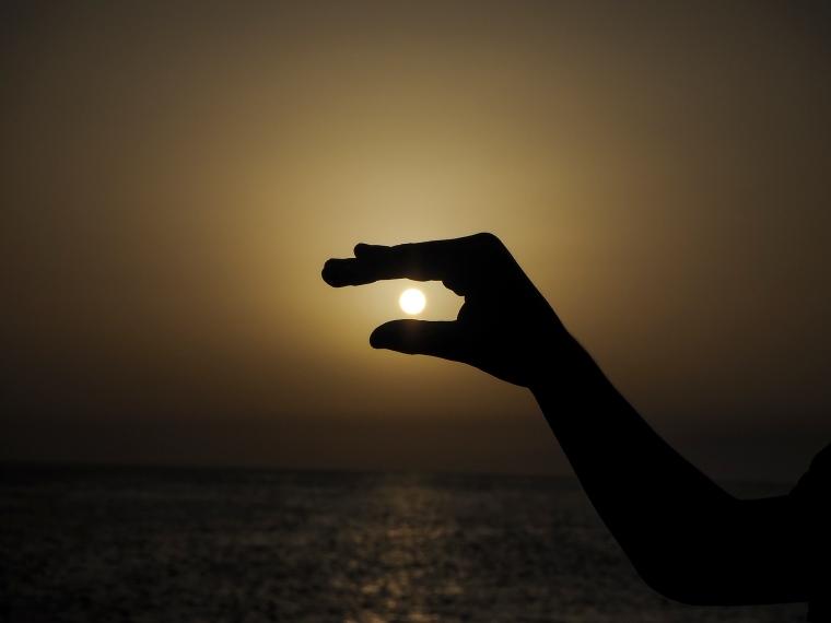 """Hand i motljus som """"håller"""" i solen"""