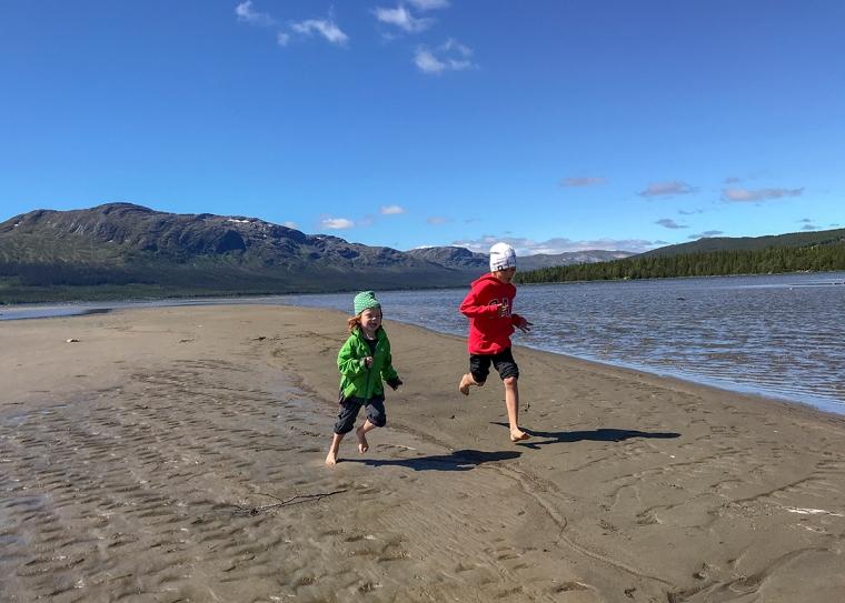 Två barn springer ikapp på stranden.