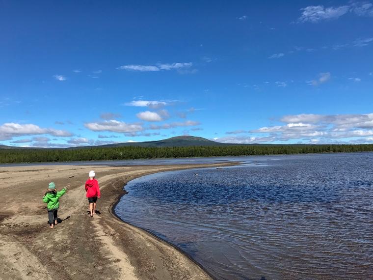 Två barn som går på en strandremsa.