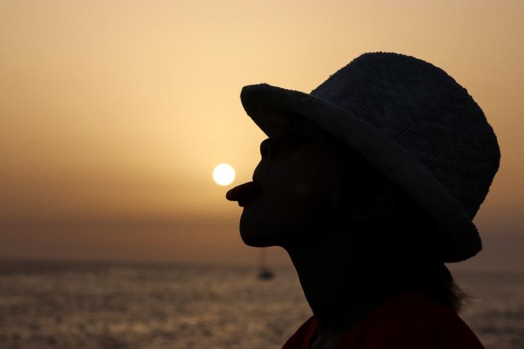 Barn som lipar i motljus så att solen ligger på tungan