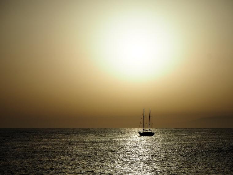 Solnedgång med en segelbåt