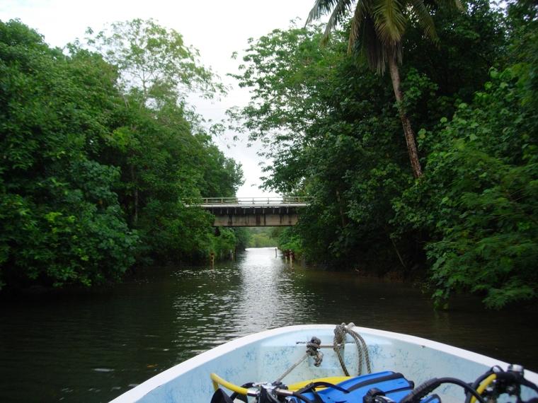 En kanal med en bro över. Fören på en dykbåt i förgrunden.