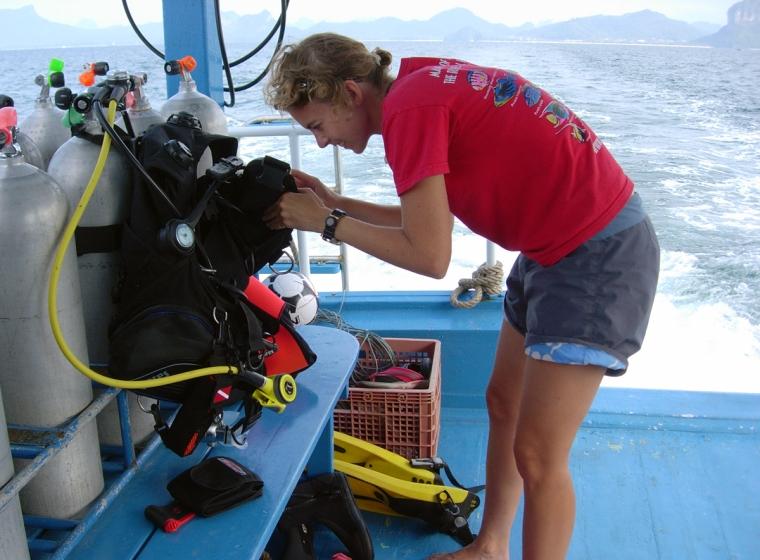 En tjej står på däck på en båt och håller på med dykutrustning.