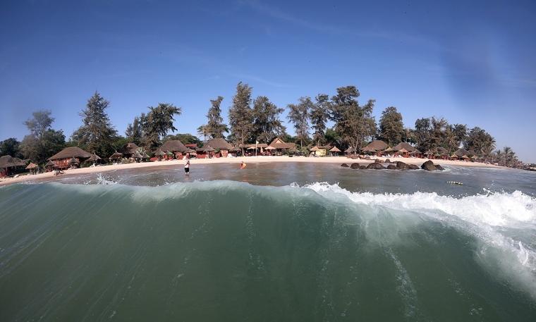 Bilde från havet mot strand med bungalows.