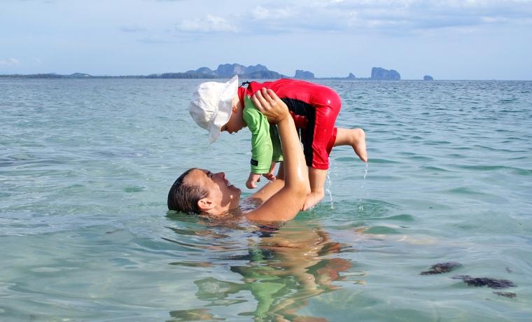 En kvinna lyfter ett barn över huvudet i havet.