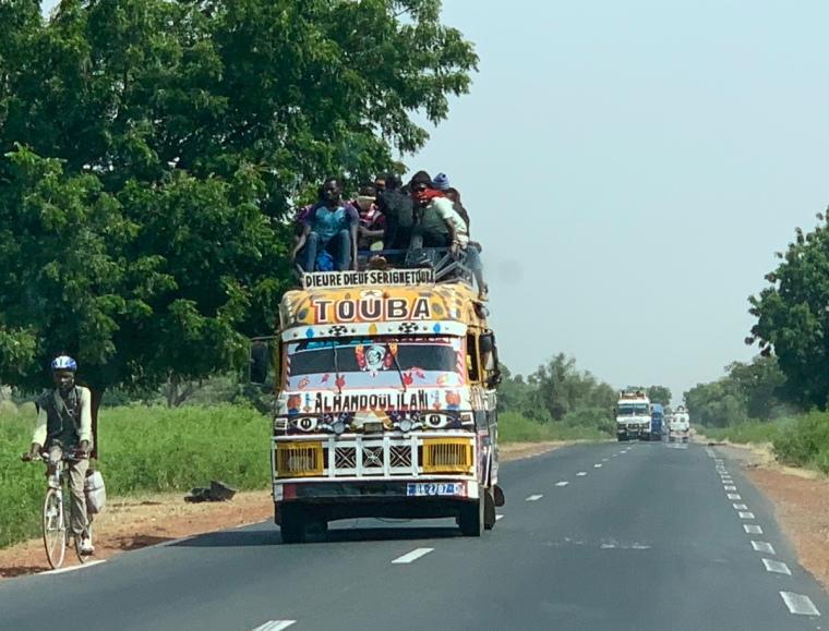 En överfull färgglad buss med människor på taket.