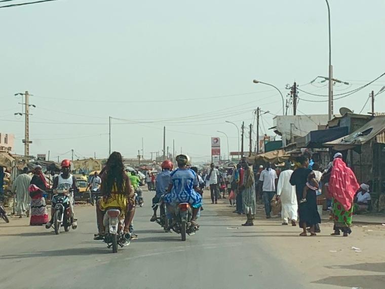 En gata full med människor, bilar och motorcyklar.