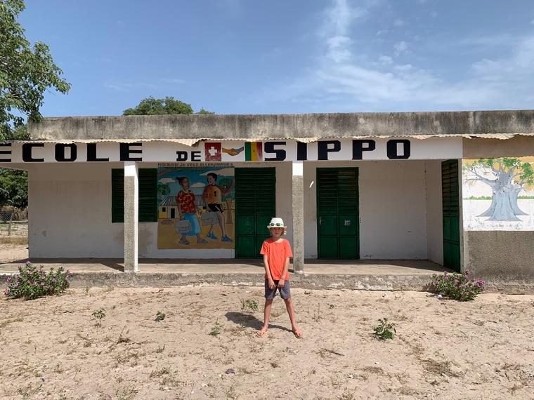 Ett barn utanför en enkel vit skolbyggnad