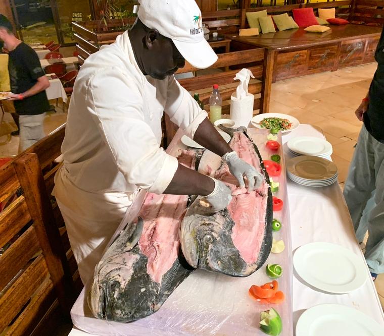 En kock som står och skär upp två stora fiskar.