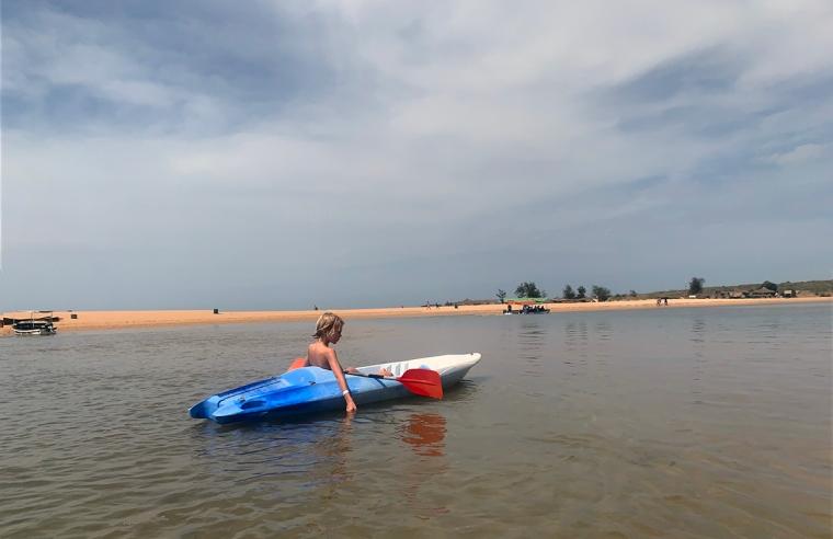 En pojke i en kajak. Strand i bakgrunden.