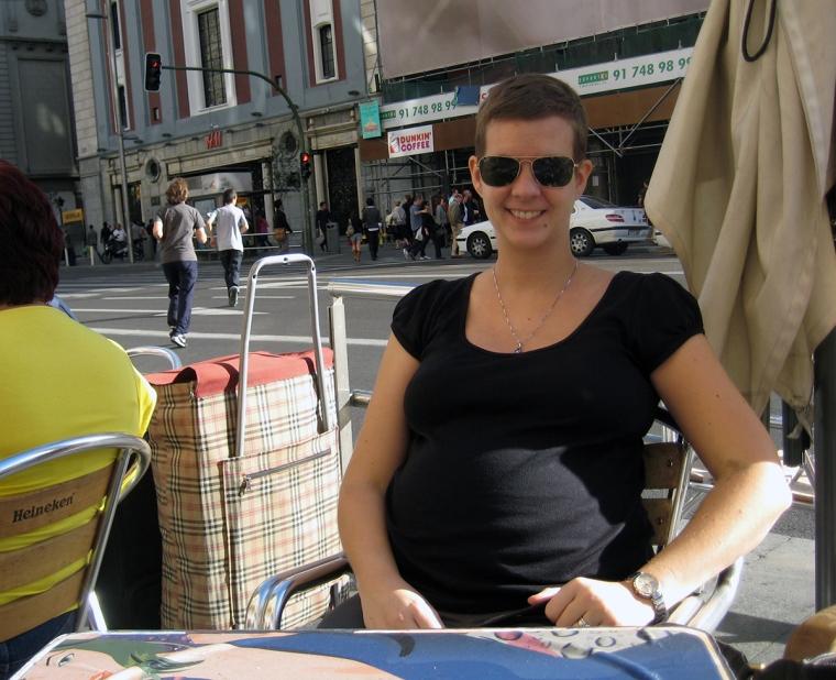 Gravid kvinna vid ett bord. En gata i bakgrunden.