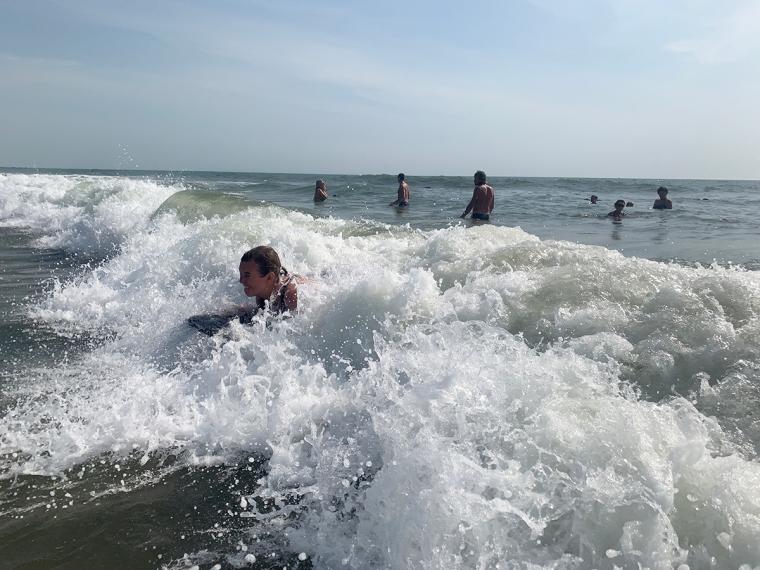 En kvinna surfar i vågorna.