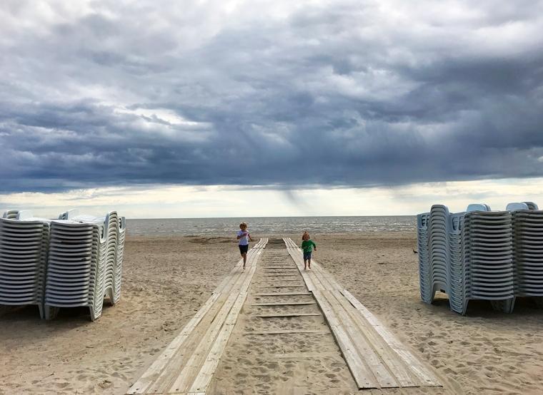 Två barn springer på en strand. Låga mörka moln över vattnet.