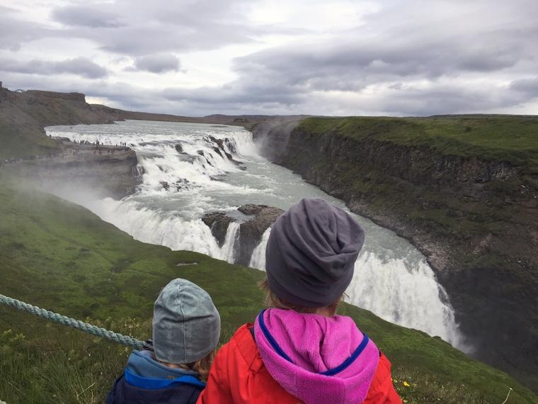 Ryggen på två barn som står vid ett stort vattenfall.