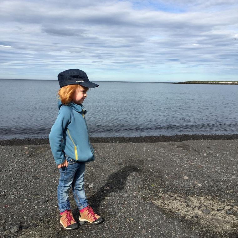 Ett barn på en svart strand med havet i bakgrunden.