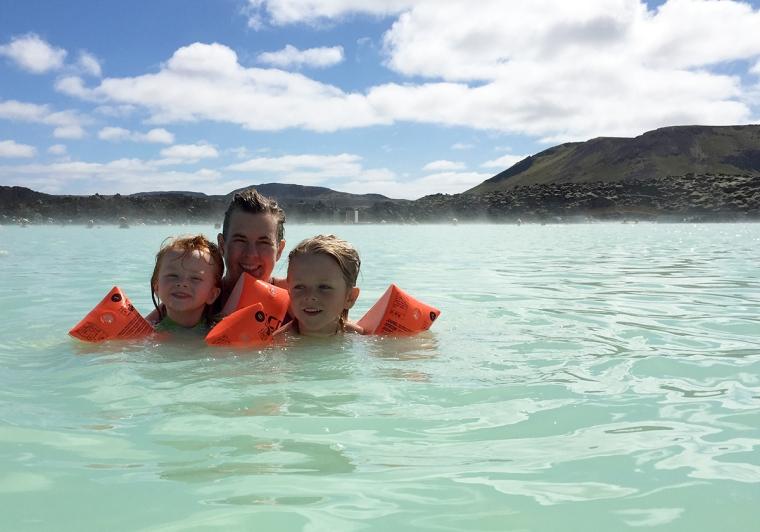 En kvinna och två barn i turkosskimrande vatten.