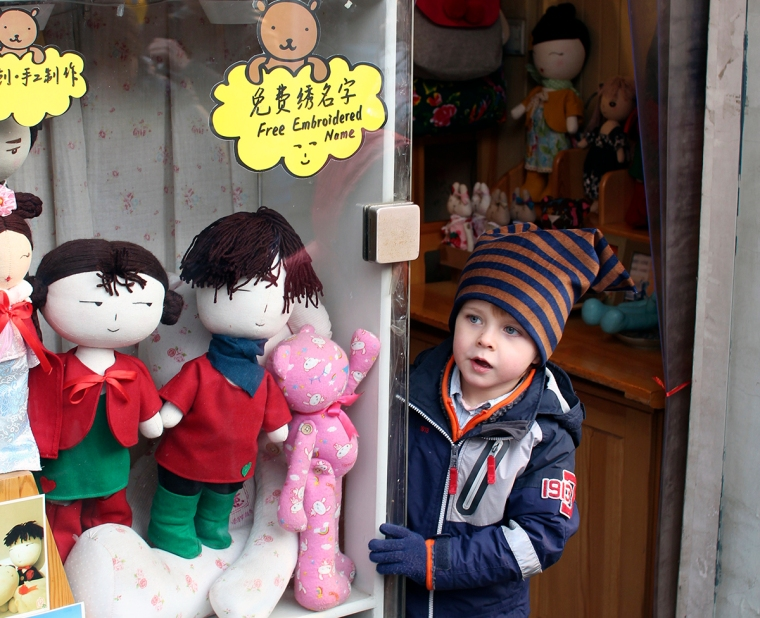 Ett barn tittar ut ur en butik. Dockor i skyltfönstret.