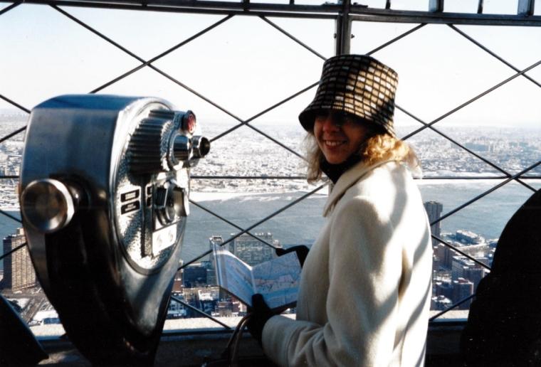 En kvinna med en karta i handen och en utsikt över en storstad.