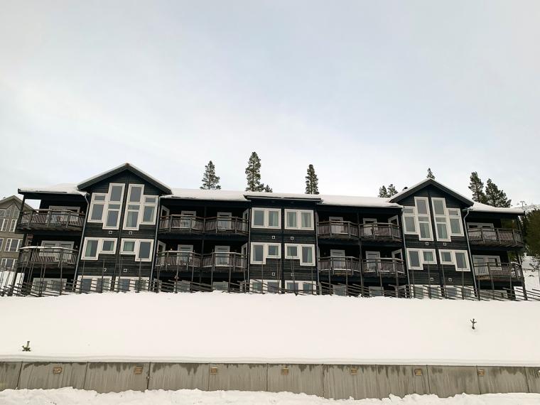 Ett bruntgrått trevåningshus med balkonger och vita fönster.