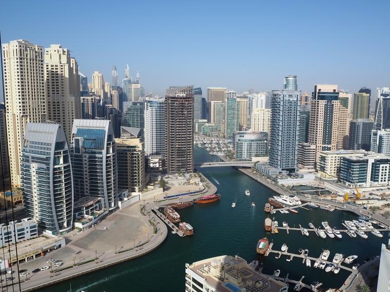utsikt över skyskrapor och vatten med stora båtar.