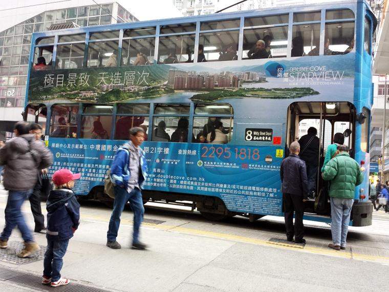 Ett barn står och tittar på folk som går på en tram.