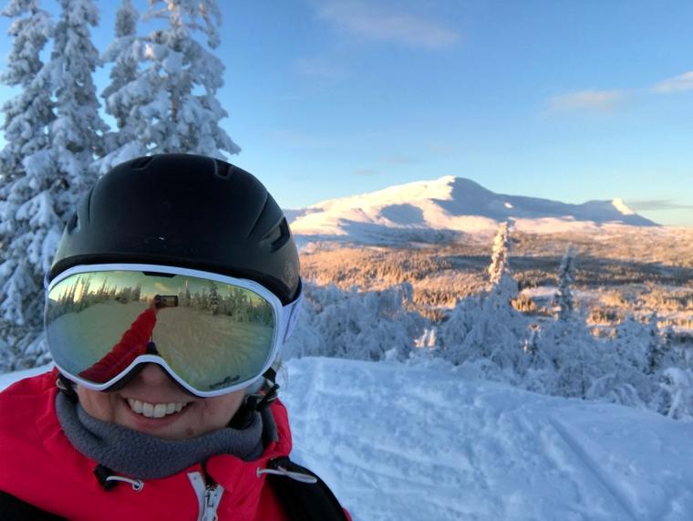 En skidåkare som tar en selfie med ett snöklätt berg i bakgrunden.