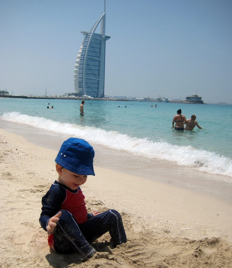 Ett barn på en strand med en byggnad som liknar ett båtsegel i bakgrunden.