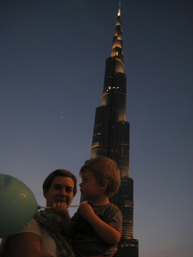 En kvinna och ett barn på kvällen framför ett högt torn.