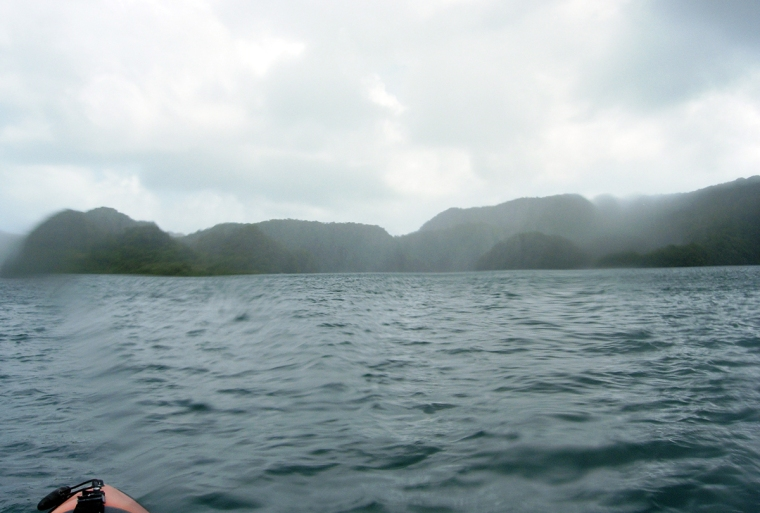 Spetsen på en kajak och regnöver havet.