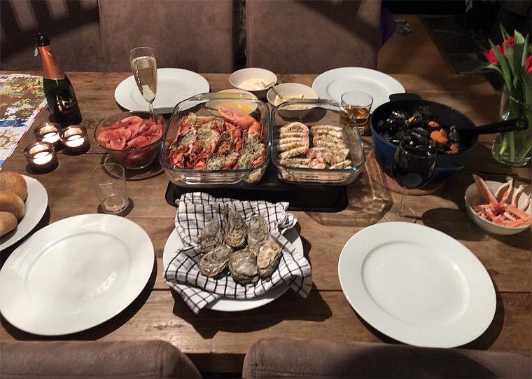 Bord dukat med räkor, musslor, havskräftor, hummer och ostron.