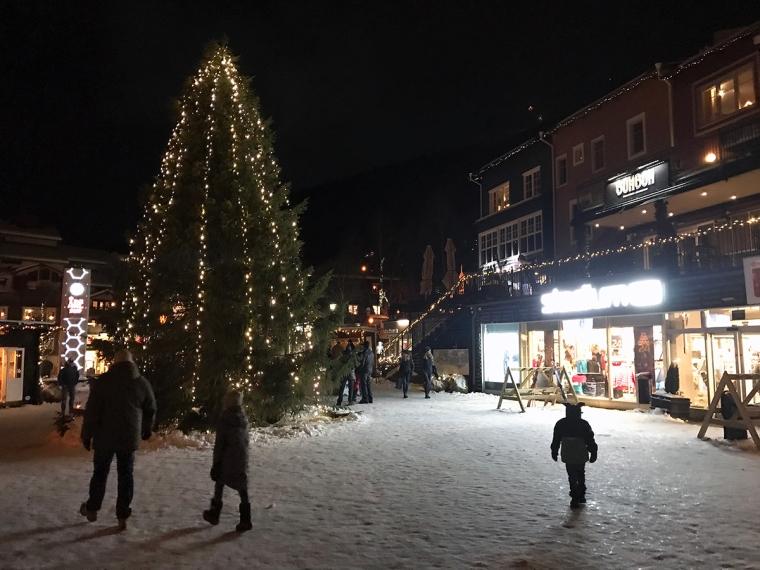 Ett torg med snö och en stor julgran.