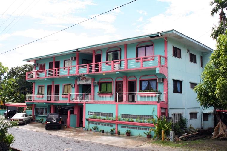 Ljusblått trevåningshus med rosa balkonger och fasaddetaljer.