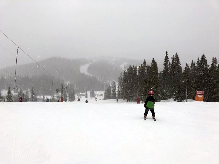 Skidbacke, ett barn bakifrån, snöfall.